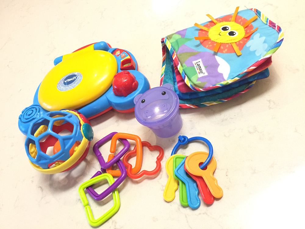 Figure: Early stage toys: Vtech mucical laptop, plastic keys, rings, soft book, a cup with a lid, rattling ball.