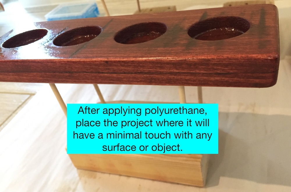 Drying a wood project after applying  polyurethane is tricky. We used a homemade platform with four pointy sticks.